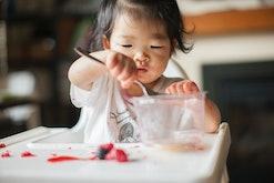 asian toddler girl eating snack
