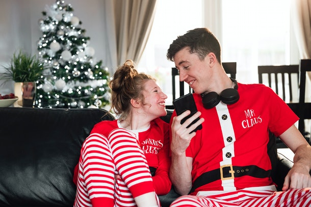 A happy couple relaxes at home on the couch in matching holiday PJs.