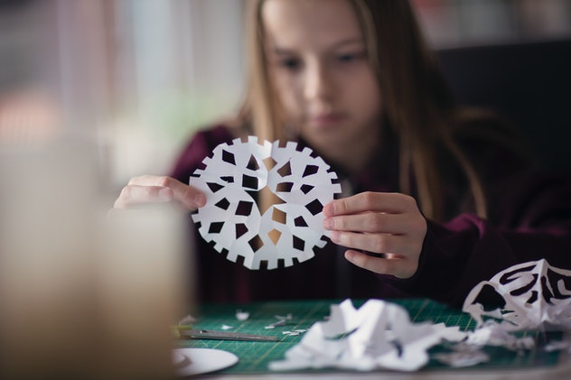girl cutting out paper snowflake