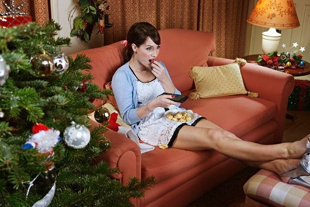 A woman eats some chocolate while sitting on her couch, watching a holiday movie on TV, and next to her Christmas tree.