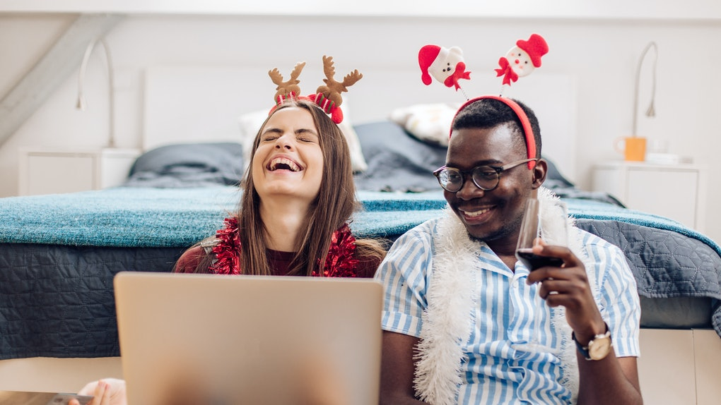 Two happy friends wear festive accessories while laughing and looking at a laptop on Christmas.