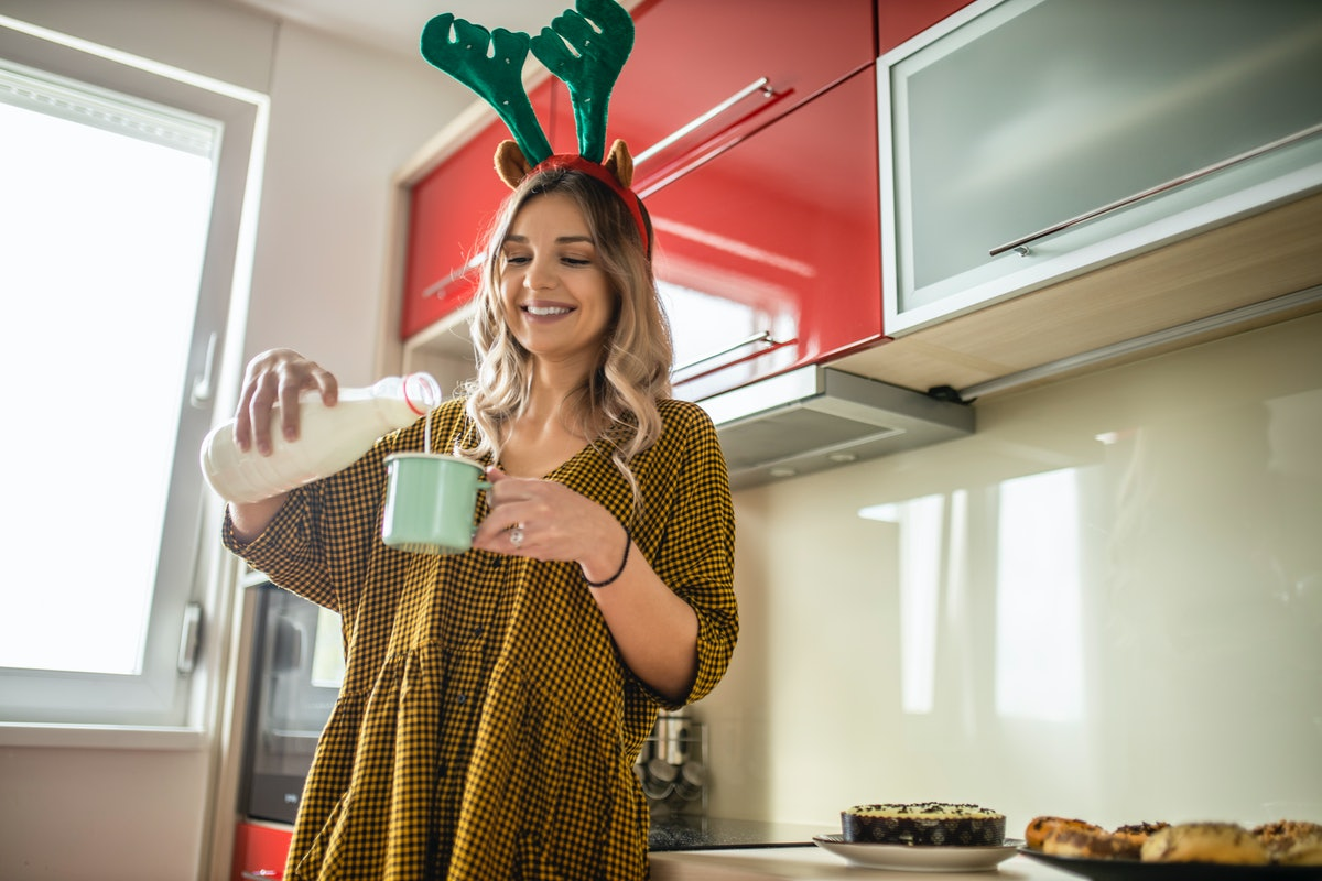 A happy blonde woman pours milk into her mug on Christmas.