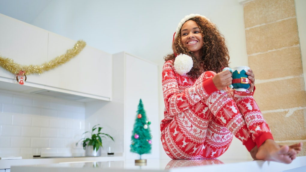 A happy woman in Christmas PJs sits on her kitchen counter and holds a festive mug of coffee.