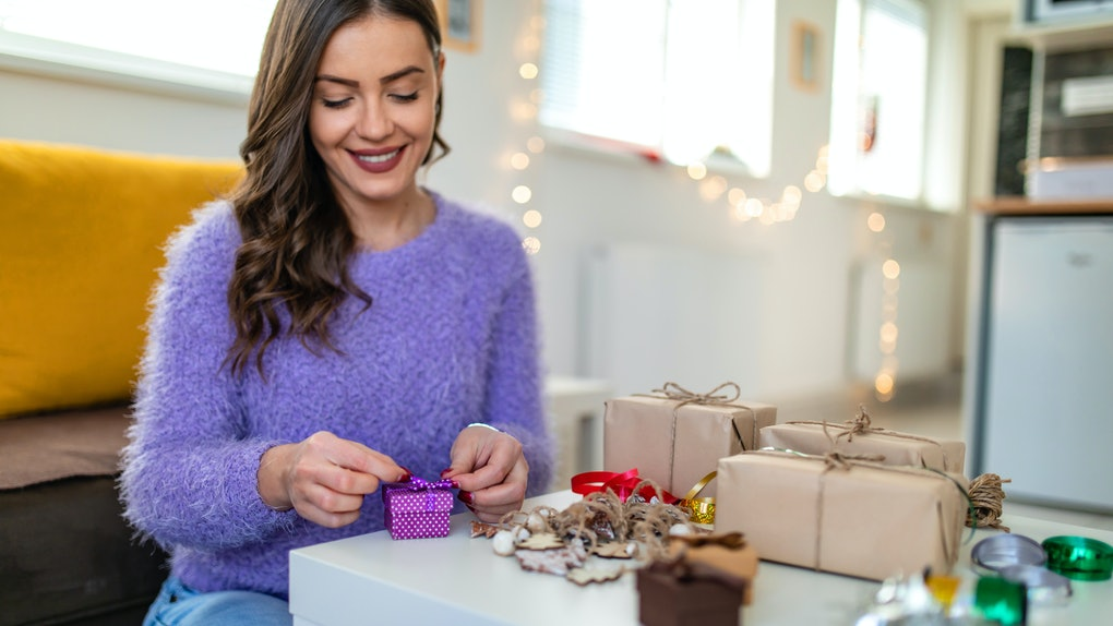 A girl is having fun making her Christmas gifts by decorating presents with bows, ribbons, brown paper packaging.