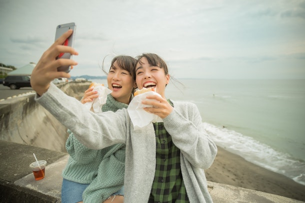 A young Asian couple takes a selfie while enjoying sandwiches near the shore.