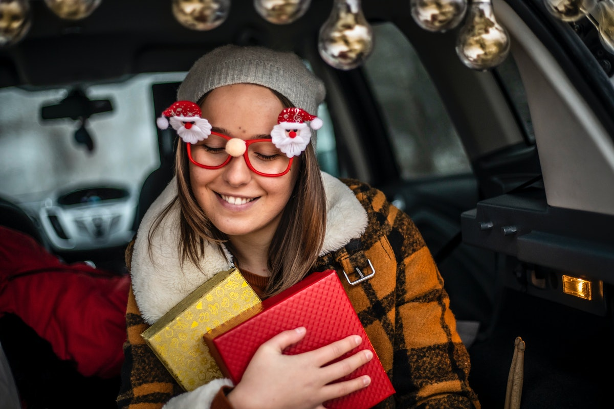 A woman wearing Santa glasses, holds onto two wrapped Christmas presents.