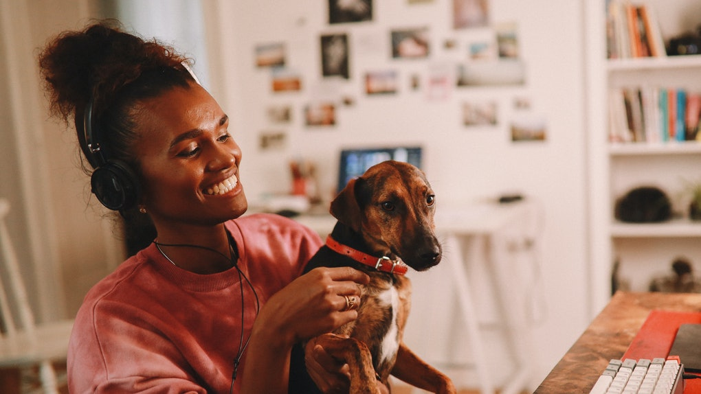 A young Black woman sits at her desk in her home office in a rose-colored crewneck, while holding her dog and wearing headphones.