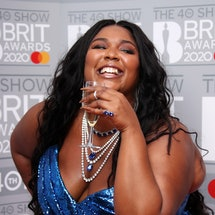 Lizzo smiles and raises a glass on the red carpet. Self-love can be hard, but it's a good habit to get into.
