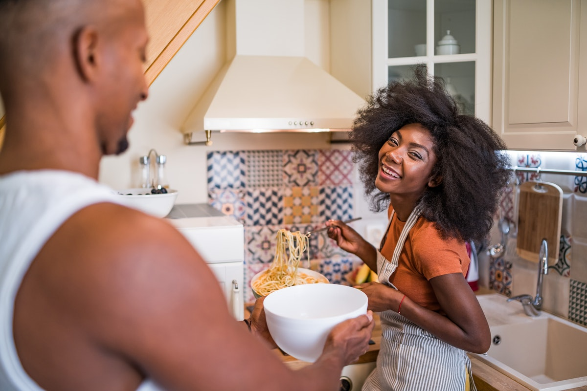 A young Black woman laughs while spooning pasta into a bowl that her partner is holding.