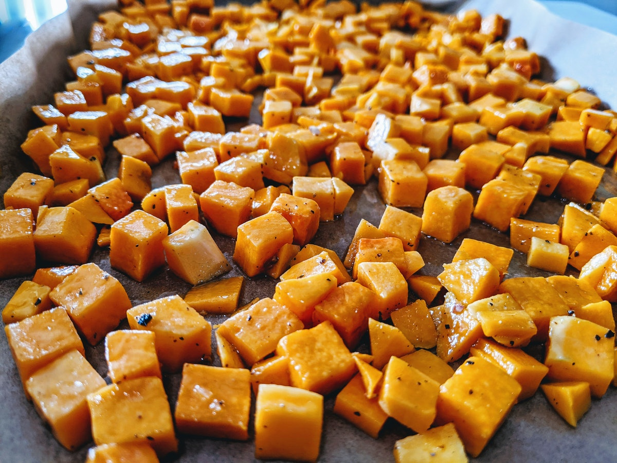 Cubes of butternut squash lay on a large baking pan while covered in olive oil and spices.