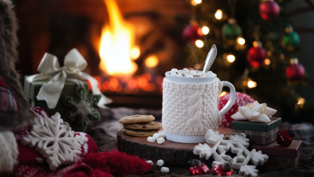A holiday mug is surrounded by Christmas decor and fake snowflakes, with a fireplace and Christmas tree in the background.
