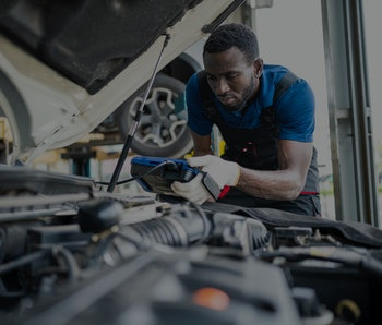 Auto technician looking under the hood of a car.