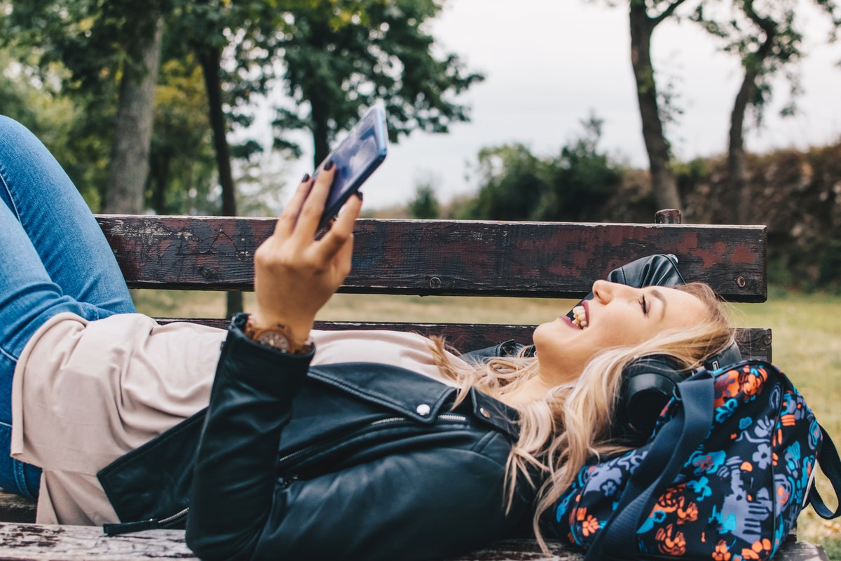 A blonde woman laughs while laying down on a bench on a sunny day in a park.