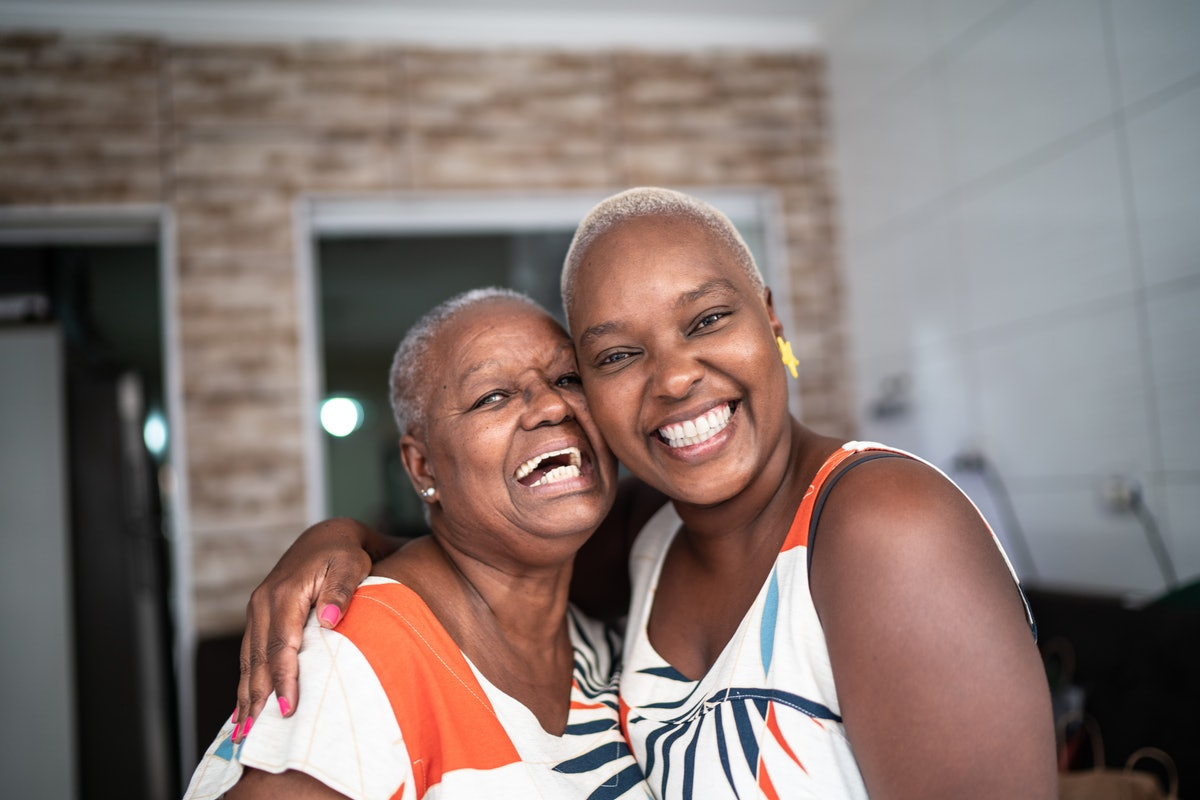 A happy mother and daughter hug while wearing matching outfits.