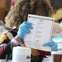 Fulton County election workers examine ballots while vote counting, at State Farm Arena on November 5, 2020, in Atlanta, Georgia. Ballot curing volunteers help Georgia voters fix technical ballot errors.