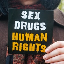 """A person holds up a small sign that reads, """"sex, drugs, human rights."""" Decriminalizing drugs in the 2020 election is a huge victory for public health and racial justice."""