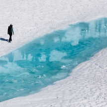 A person stands next to a frozen river. Winter mental health tips allow you to get creative.