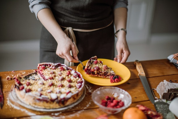 A woman slices out a piece of pie and puts it on a plate.