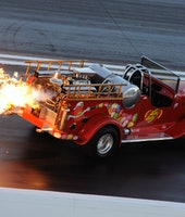 Red truck spitting flames out of its exhaust on a race track.