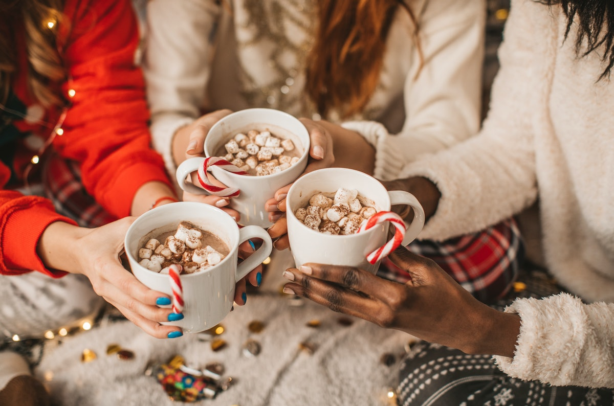A group of friends holds mugs of hot cocoa, candy canes, and marshmallows together while sitting on a shaggy rug.