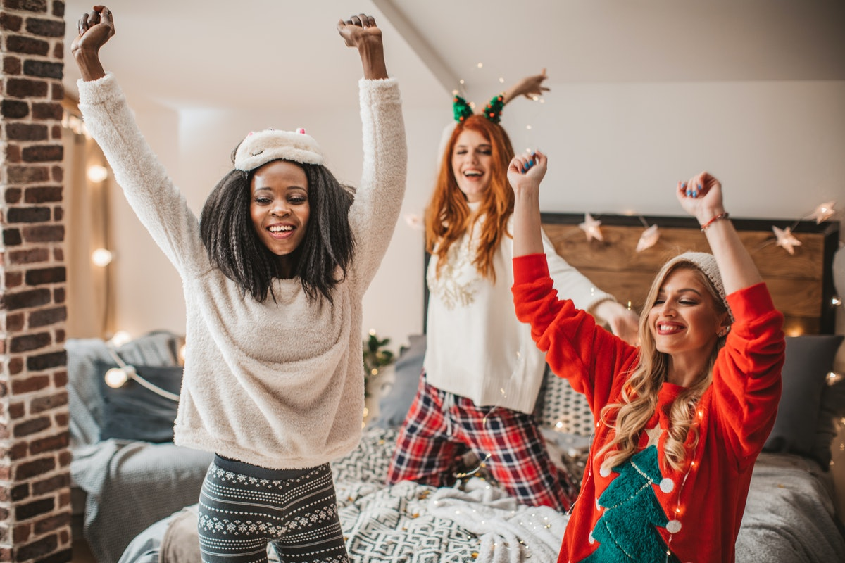 Three happy friends dressed up in holiday loungewear dance around in a bedroom.