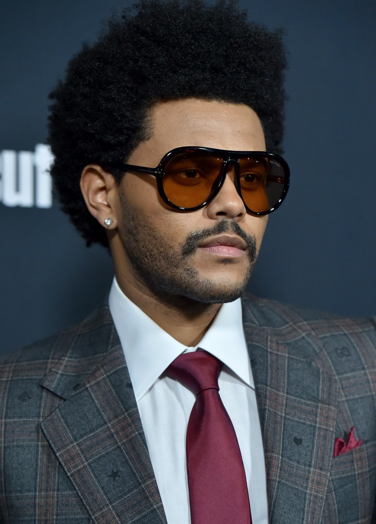 The Weeknd hits the red carpet wearing black sunglasses.