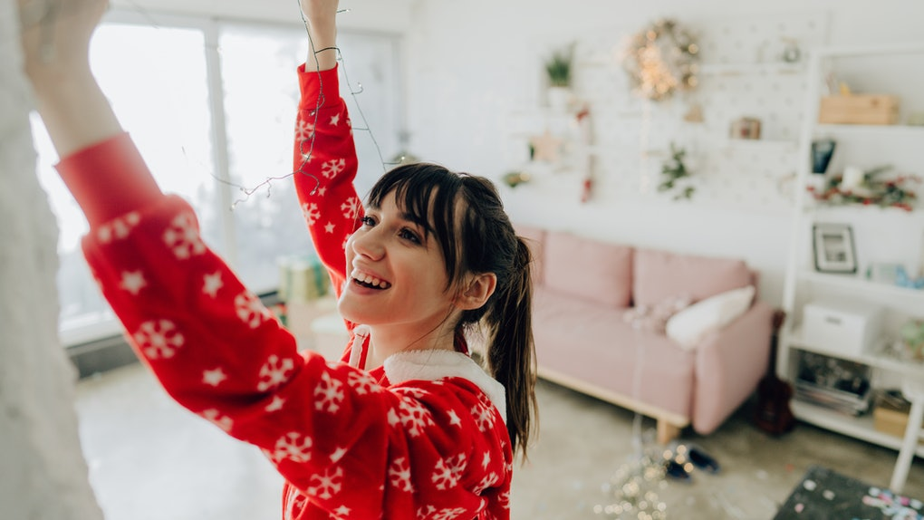 A young woman hangs holiday lights in her apartment that's very cozy and minimalistic.
