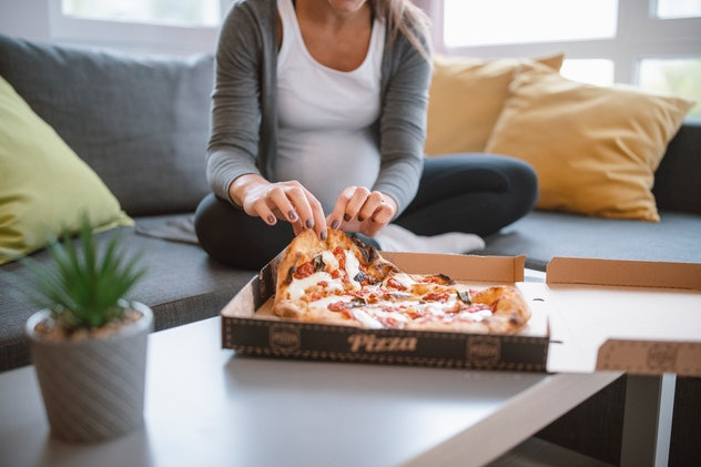 pregnant woman eating Jalapeno poppers pizza