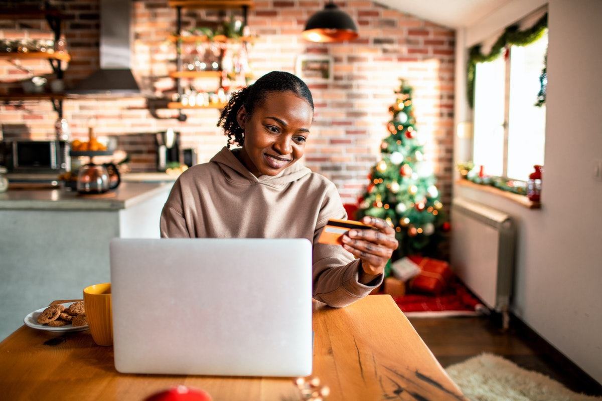 A young Black woman sits at her kitchen table and shops a virtual holiday market on her laptop.