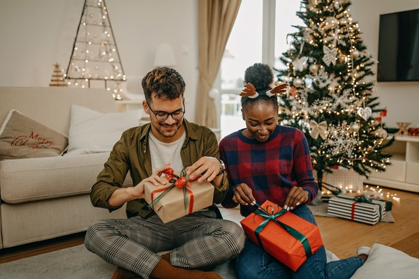 Two housemates sit on their living room floor near a Christmas tree and exchange gifts.
