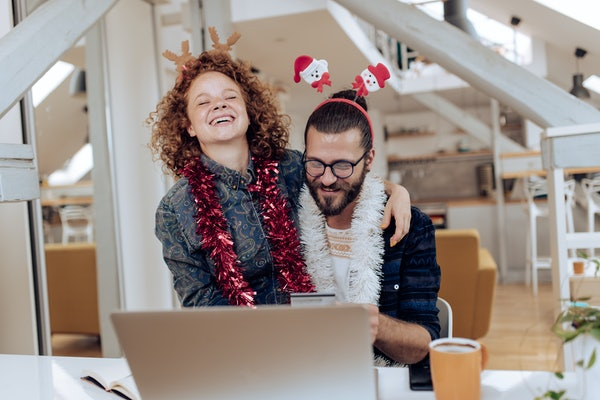 A young couple laughs while participating in a virtual holiday 2020 experience at home and wearing holiday outfits.