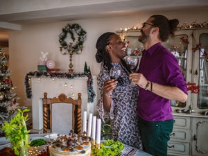 A happy couple embraces and holds their glasses of wine in a cozy Christmas home.