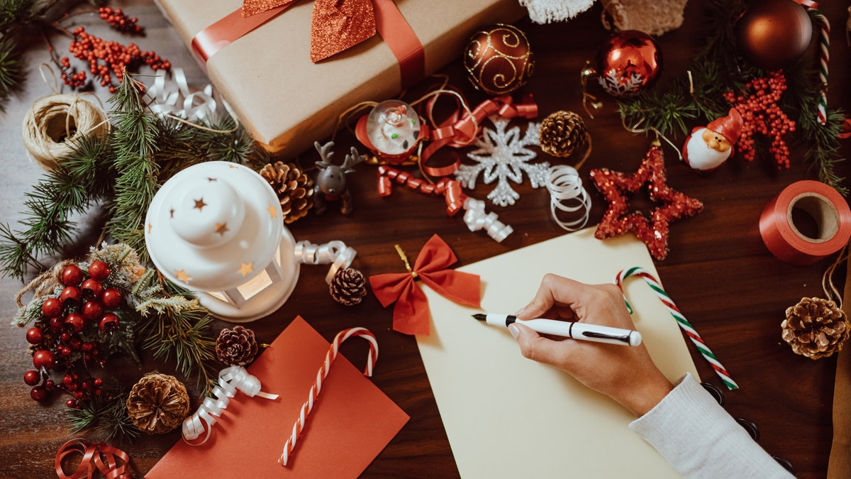 A young woman writes a wish list on a blank sheet of paper surrounded by Christmas decorations.