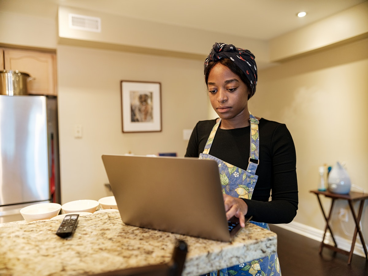 A woman types on her laptop in her kitchen while taking a virtual holiday cooking class.
