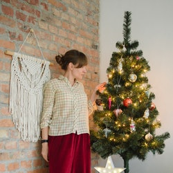 A woman in a sweater and red pants stands next to a small christmas tree. Experts share advice for feeling sad around the holidays.