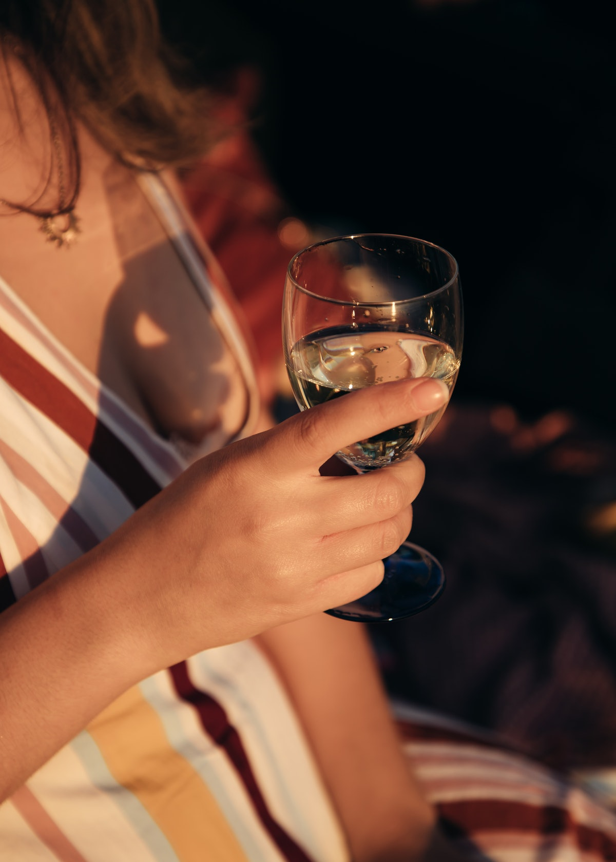 A young woman holds a champagne glass in her hands at golden hour.