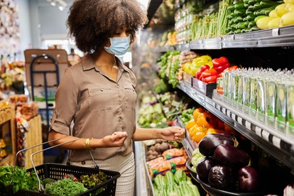 A woman buys groceries while wearing a mask. Doctors explain the best time to go grocery shopping during the pandemic.