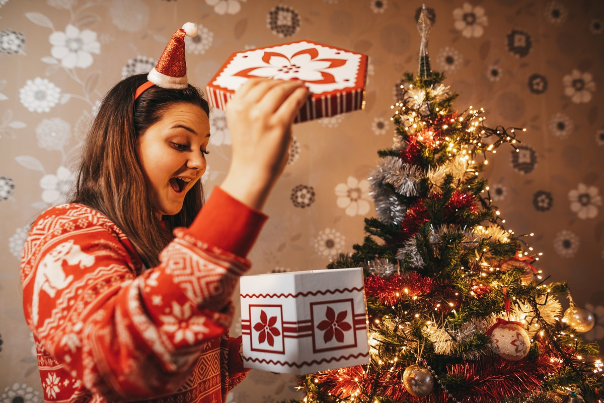 A happy woman in a festive Christmas sweater opens a holiday-themed box for Secret Santa.