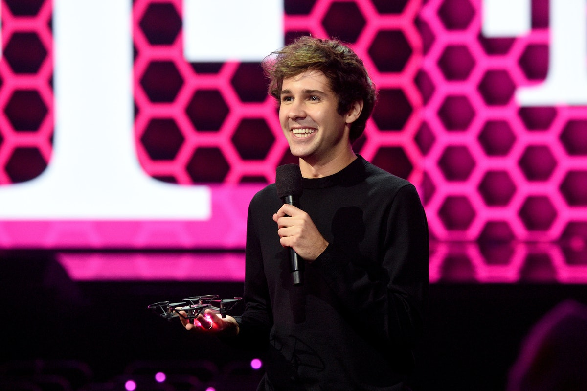"""David Dobrik, YouTuber behind """"The Hundred Thousand Dollar Puzzle,"""" stands with a microphone at the American Music Awards."""
