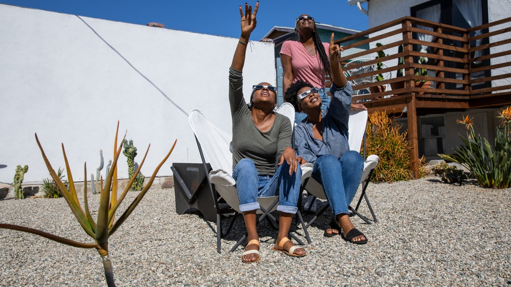 Three women look up at the solar eclipse in their solar eclipse glasses.