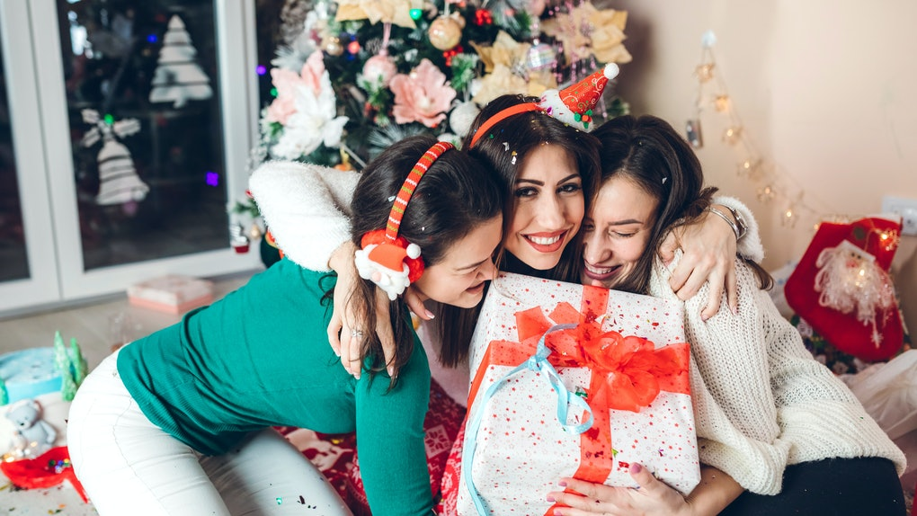 Three friends embrace, holding a Christmas present in front of a Christmas tree and lots of confetti.