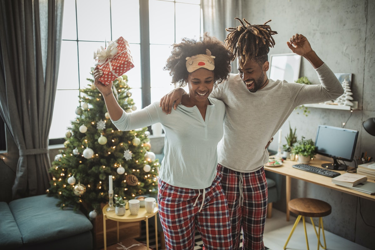 A happy couple dances in their living room in their Christmas loungewear.