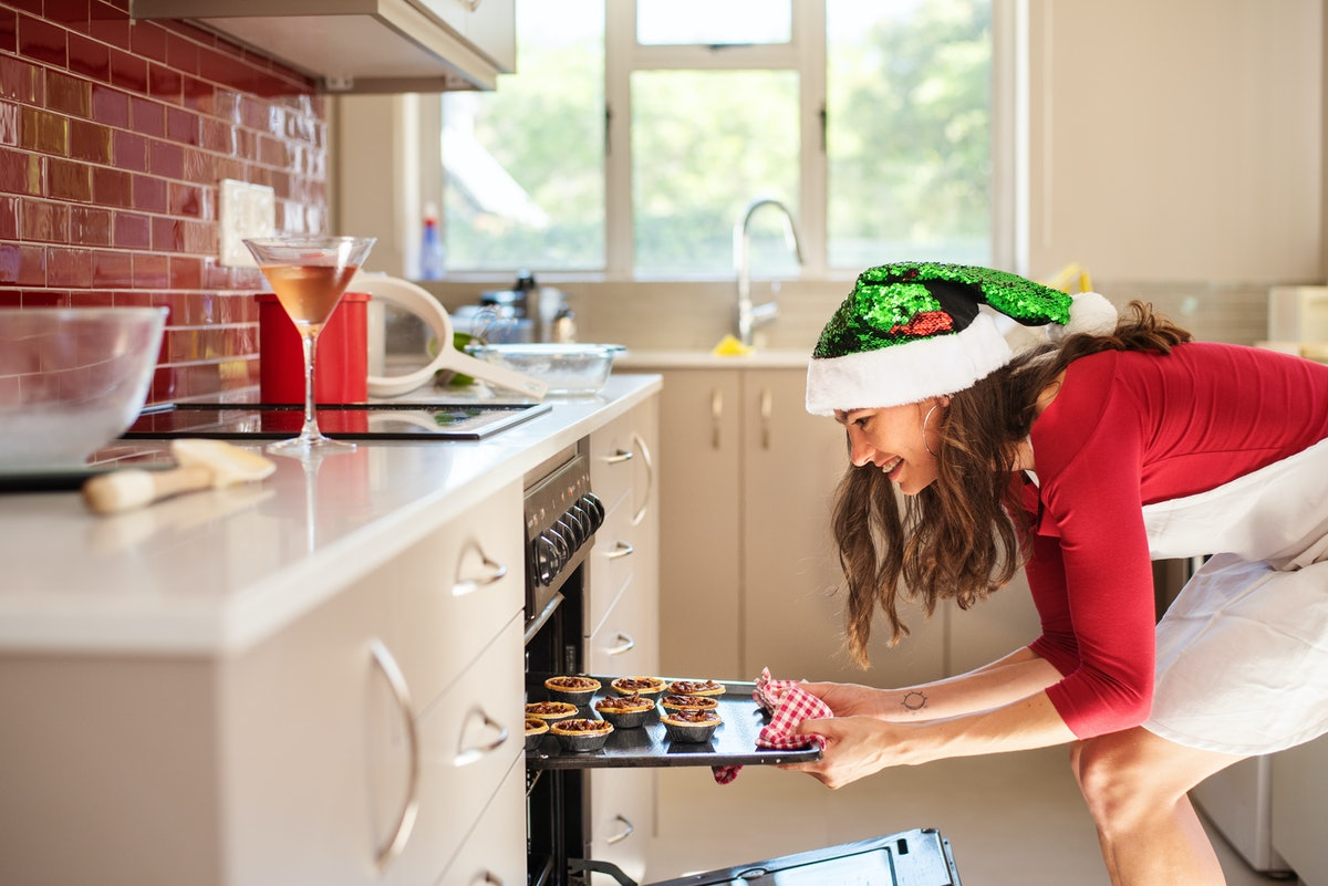 A woman dressed up for Christmas puts holiday treats in the oven to bake.
