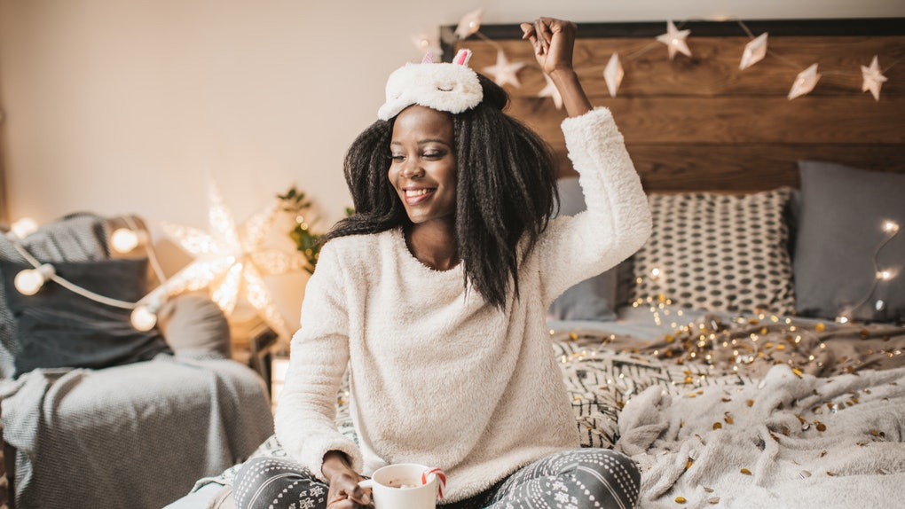 A happy woman dressed in holiday loungewear enjoys a mug of hot cocoa on her bed.