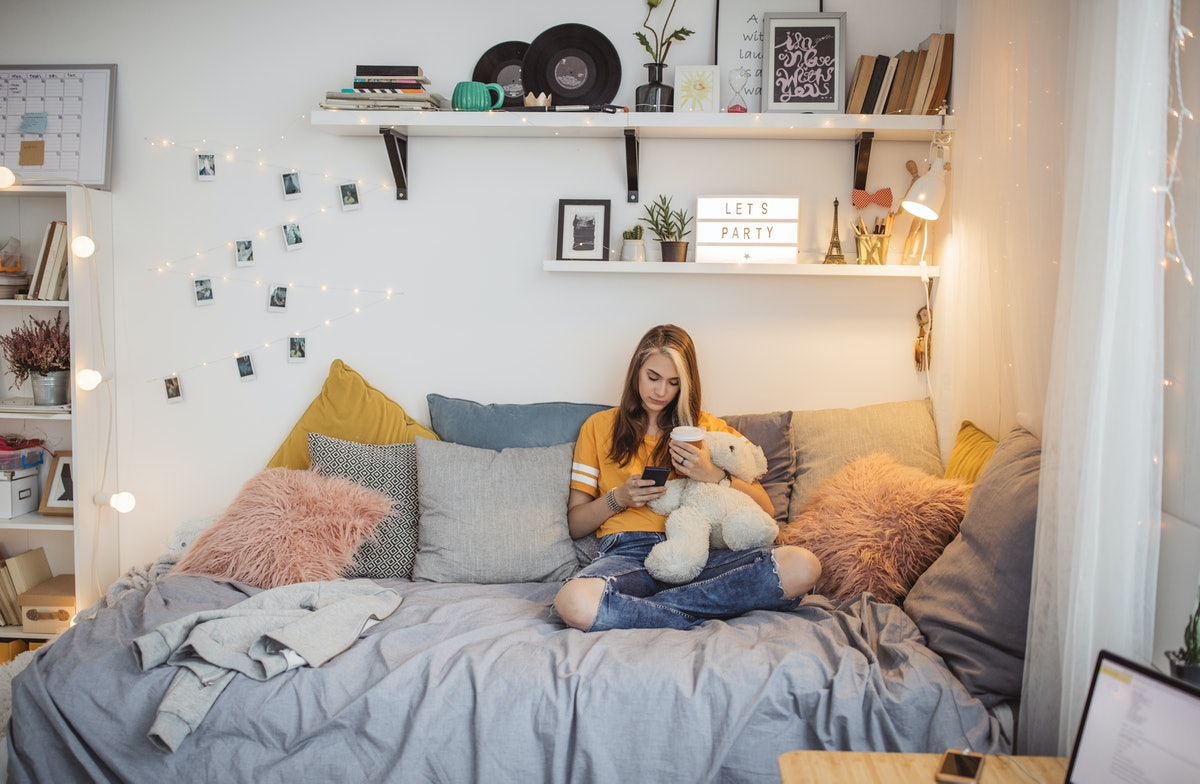 A trendy teen sits in her bedroom that's decorated in cool decor and texts.