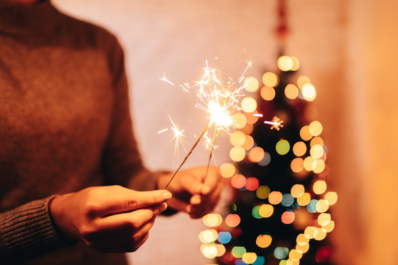 A woman holds up sparklers in front of a lit christmas tree. This year, celebrate new year's eve safely during the pandemic.
