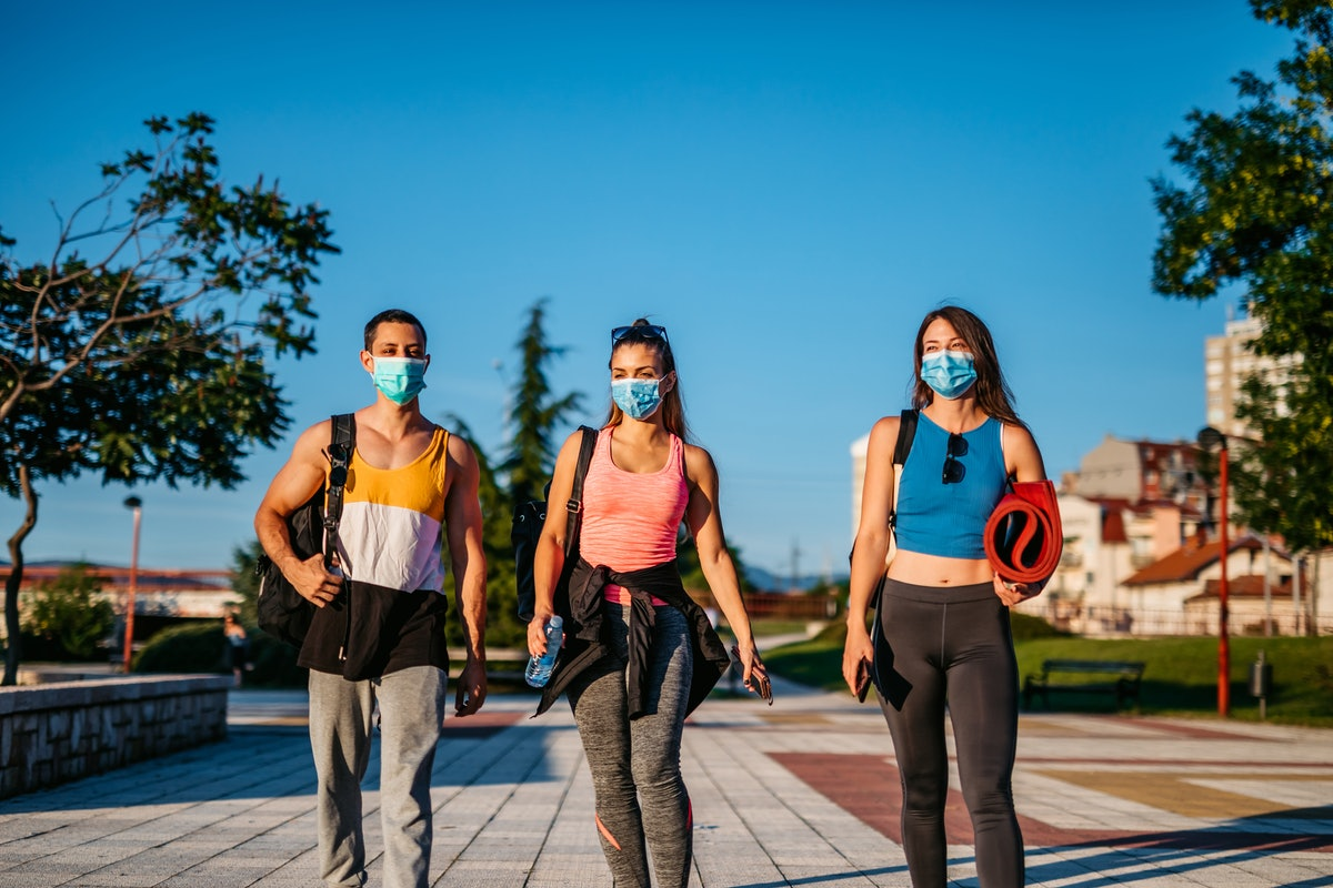 A group of masked friends walks to yoga in a park. Women worked out more than men in 2020.