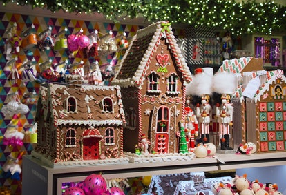 two large gingerbread houses next to a three nutcrackers.