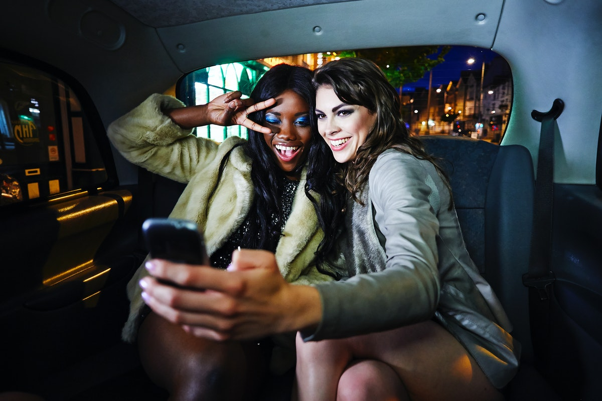 Two young women pose for a selfie while experiencing a drive-thru Christmas light show.