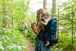 mom on hike in woods with baby on back